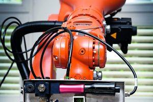 Kooperation_intelligenter_Maschinen:_Der_Robotergreifer_übergibt_ein_Werkstück_an_eine_bewegliche_Plattform,_die_es_zum_nächsten_Arbeitsschritt_fährt.__Ob_Möbel,_Kleidung_oder_Kugelschreiber_–_als_Massenprodukte_werden_Industriegüter_besonders_kostengünst