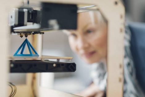 Mature_smiling_woman_working_by_3d_printer._Selective_focus_to_object_in_the_3D_printer._She_is_starting_printing_process_for_her_new_3d_project.