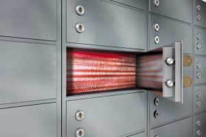 A_closeup_of_a_wall_of_closed_metal_safety_deposit_boxes_with_one_open_revealing_its_contents_inside