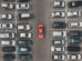 Top_view_of_the_crowded_Parking_lot_with_quadcopter_or_drone._Original_bright_automobile_among_the_grey_of_mediocre_cars._Parking_space_search,_No_parking_space.