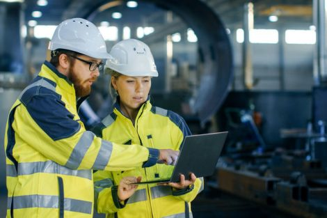 Male_and_Female_Industrial_Engineers_in_Hard_Hats_Discuss_New_Project_while_Using_Laptop._They_Make_Showing_Gestures.They_Work_in_a_Heavy_Industry_Manufacturing_Factory.