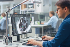 Over_the_Shoulder_Shot_of_Engineer_Working_with_CAD_Software_on_Desktop_Computer,_Screen_Shows_Technical_Details_and_Drawings._In_the_Background_Engineering_Facility_Specialising_on_Industrial_Design
