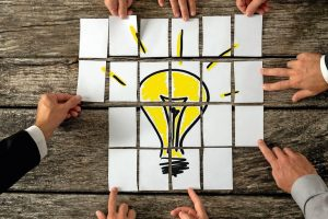 High_angle_view_of_businessmen_hands_touching_white_papers_arranged_on_a_rustic_wooden_table_forming_a_yellow_light_bulb._Conceptual_for_bright_business_ideas_and_innovations._