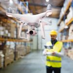 Man_or_a_worker_with_drone_standing_in_a_warehouse.