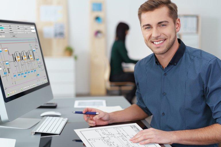 lächelnder_mitarbeiter_im_büro_arbeitet_am_pc